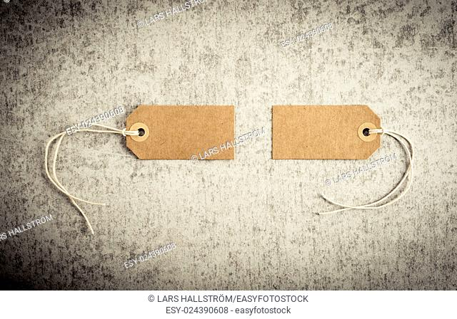 Two blank paper tags on stone background. Concept of sale, shipping or retail pricing