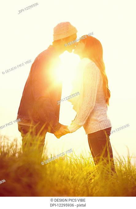 Young Couple in Love, Kissing at Sunset