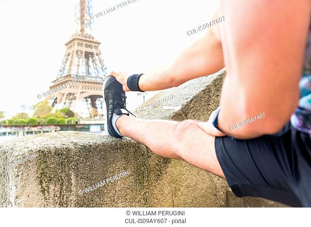 Young man exercising outdoors, stretching, rear view, Eiffel Tower in background
