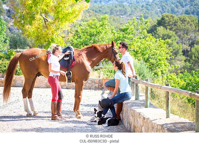 Female groom with horse and horse riders at rural stables
