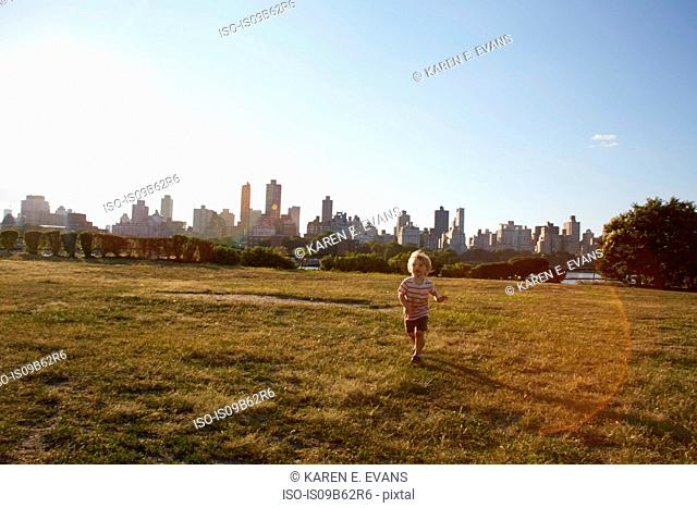 Boy running in park in front of New York skyline, USA