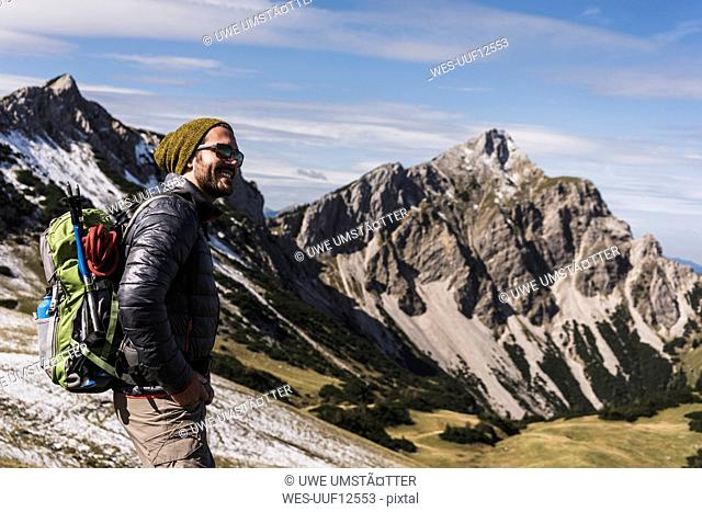 Austria, Tyrol, smiling young man on a hiking trip in the mountains