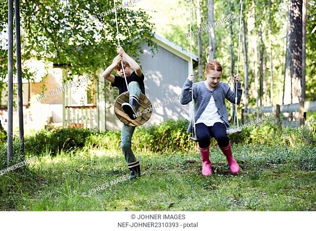 Boy and girl swinging in garden