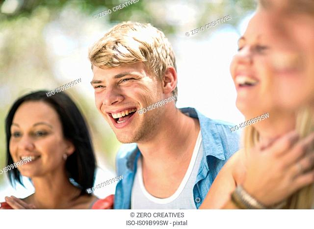 Four young and mid adult friends laughing at beach party