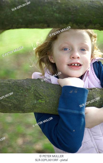 Smiling girl climbing tree