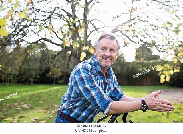 Portrait confident senior man mowing autumn lawn in backyard