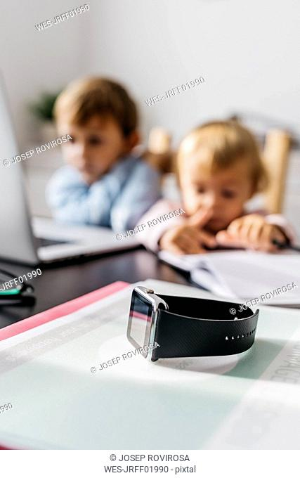 Smartwatch on a desk, with children using laptop in the background