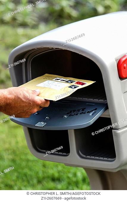 Placing a letter in the mail box for collection by the US Postal Service - Dont forget to put the red flag up though!