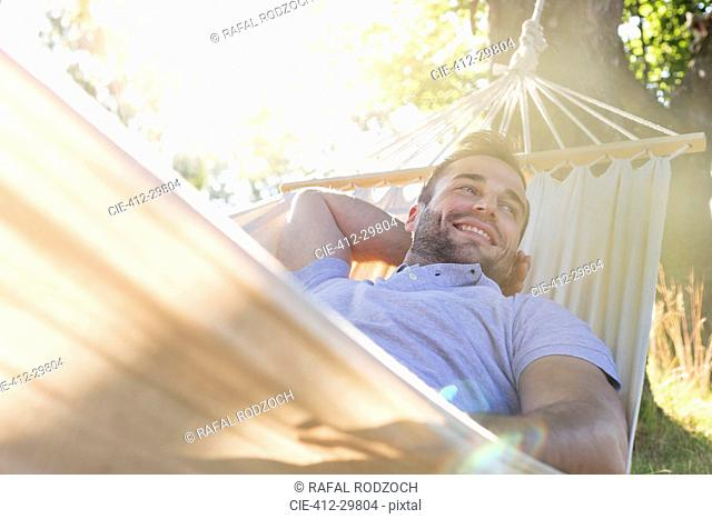Smiling young man relaxing in summer hammock