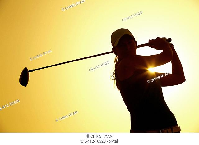 Silhouette of woman playing golf on course