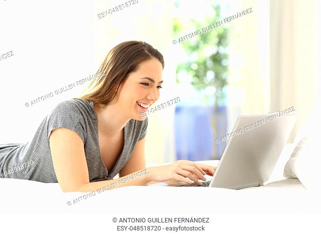 Happy lady using a laptop searching online on the bed at home