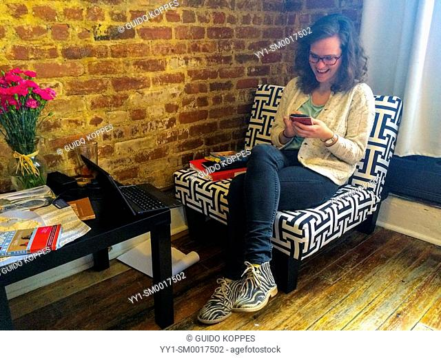 New York City, USA. Young, brunette woman having a big smile, while reading her smartphone messages