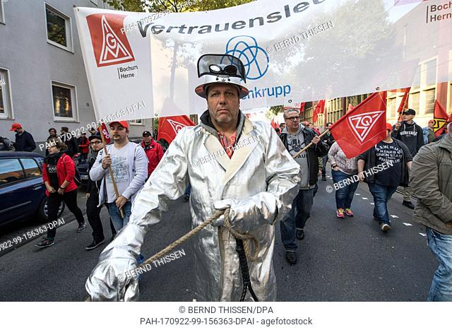 A demonstrator wears his protective clothing during a protest organised by the worker's council and the IG Metall union in Bochum, Germany, 22 September 2017
