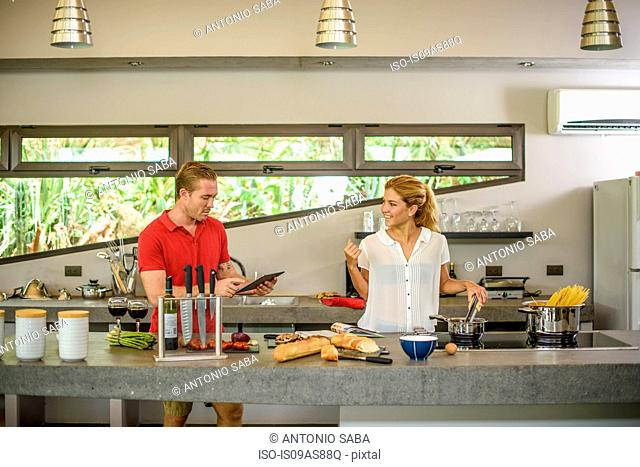 Couple preparing food and using digital tablet in kitchen