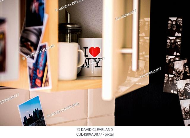 Photographs on and around semi-opened kitchen cabinet