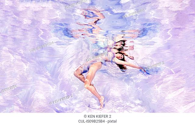 Underwater view of woman draped in sheer fabric, floating towards water surface
