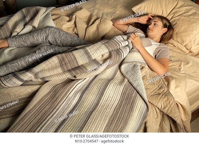 Teenage girl lying in bed