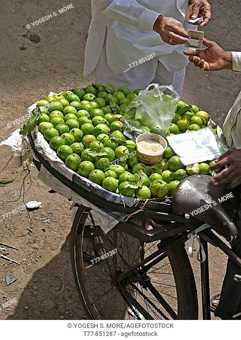 A man is paying after purchasing Guavas from a hawker
