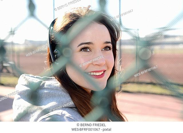 Portrait of smiling woman with headphones behind mesh wire fence