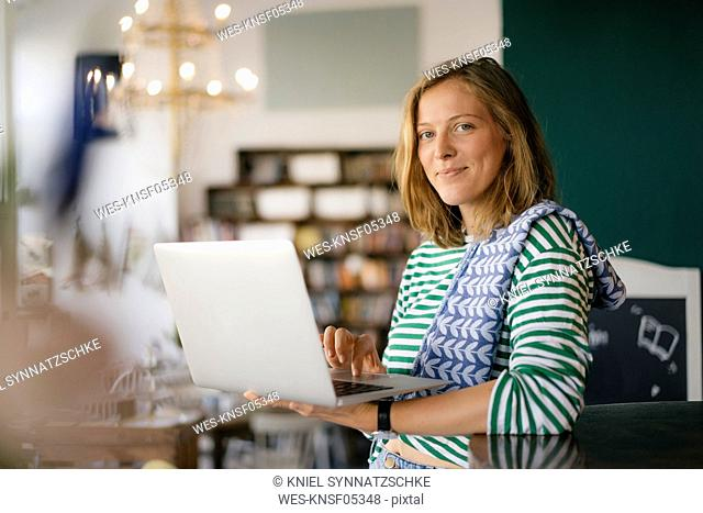 Portrait of smiling young woman using laptop in a cafe