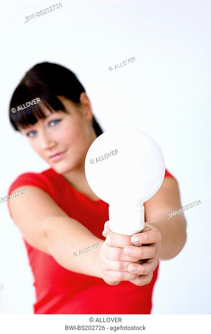 portrait of a darkhaired young woman with an electric bulb in hand