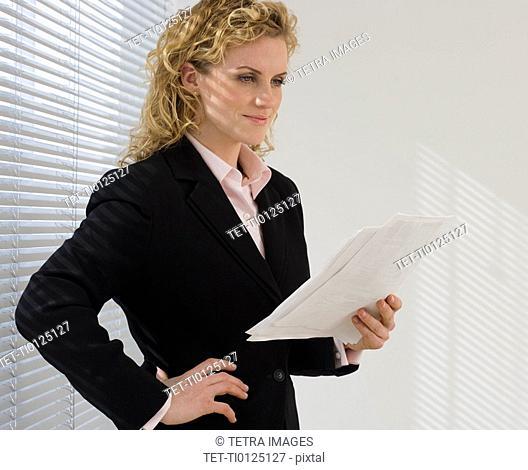 Businesswoman reading paperwork next to window