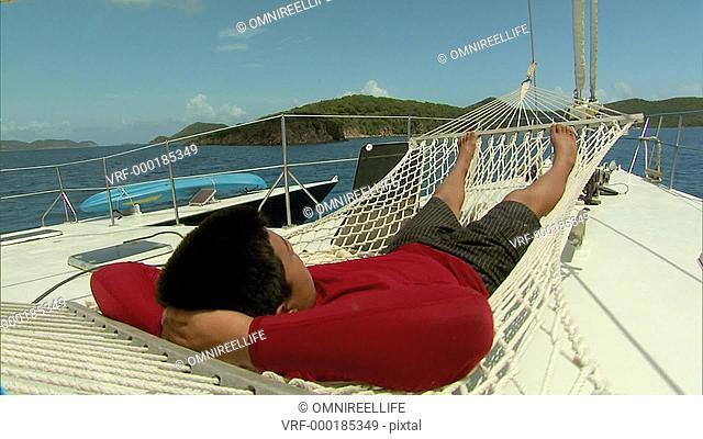 Teenage male laying on swinging hammock on boat with land and ocean behind