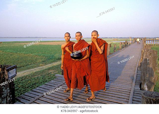 Buddhist monks crossing the U Bein's bridge at Amarapura, the longest teak footbridge in the world at 1.2 km. Mandalay region, Myanmar