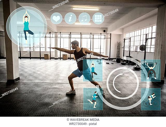 Fit man performing stretching exercise in gym against fitness interface in background