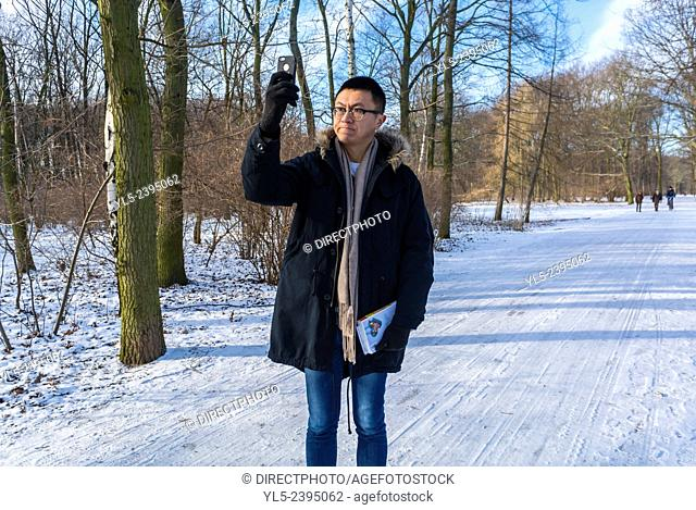 Berlin, Germany, Chinese Tourist taking Selfies Photos alone in German Public Park Scenes, Tiergarden in Winter Snow