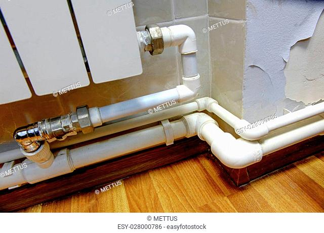 Fragment of the heater indoors and hot water pipes connected with a lot of copyspace