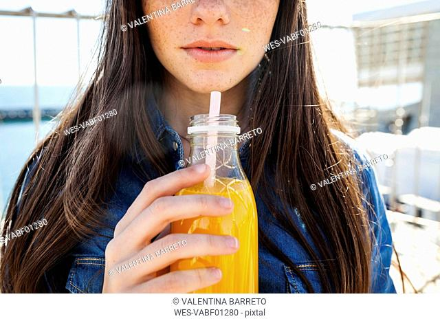 Young woman with bottle of orange juice, partial view