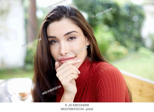 Portrait of smiling woman with hand on chin