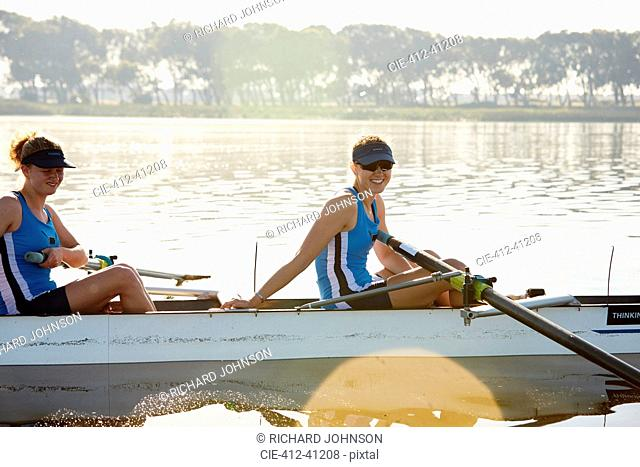 Portrait smiling female rower in scull on sunny lake