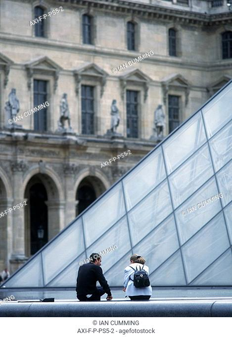 Young couple beside the pyramid in the courtyard of Louvre