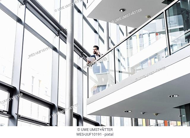 Businessman standing on landing of an office building, talking on the phone, while reading documents