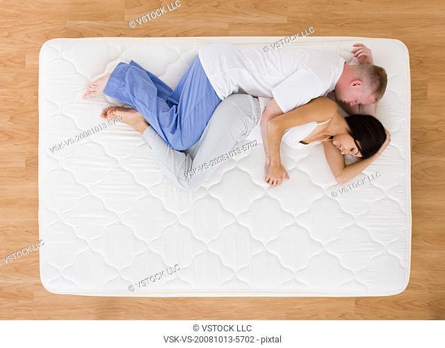 USA, Illinois, Metamora, Young couple sleeping on mattress
