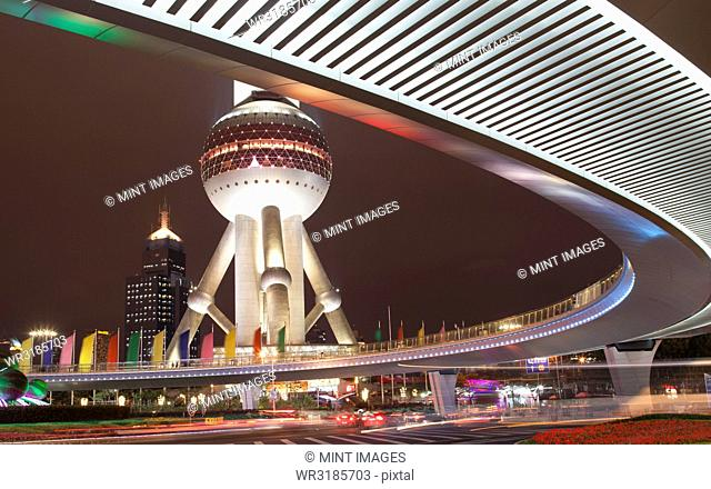Elevated road and view of the lower spherical observation deck of Oriental Pearl TV Tower, Shanghai, Pudong, China at night