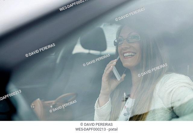 Smiling businesswoman on cell phone in car