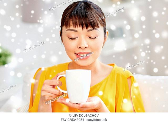 people, drinks and leisure concept - happy asian woman sitting on sofa and drinking tea from cup or mug at home over snow