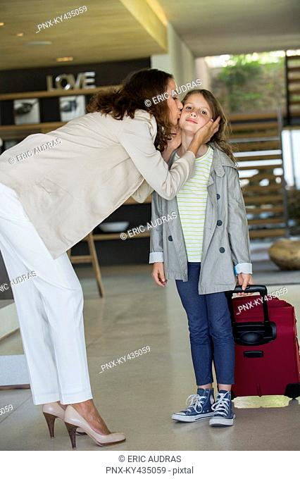 Woman kissing her daughter arriving from holiday