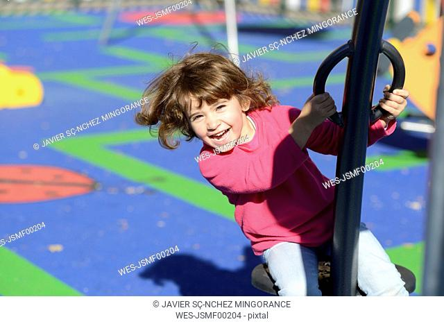 Portrait of happy little girl on playground