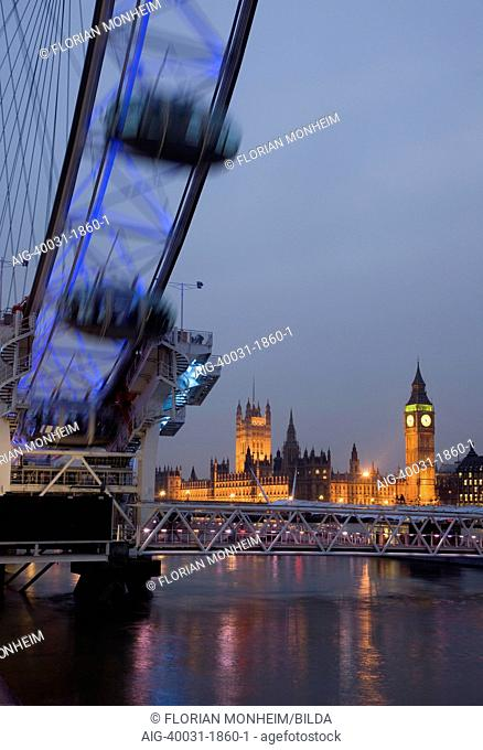 View across the River Thames, showing the London Eye wheel in the foreground and the Houses of Parliament lit up, London, UK
