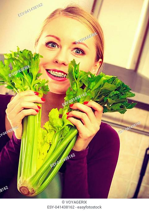 Woman in kitchen holding green fresh stemmed celery. Young housewife cooking. Healthy eating, vegetarian food, dieting and people concept