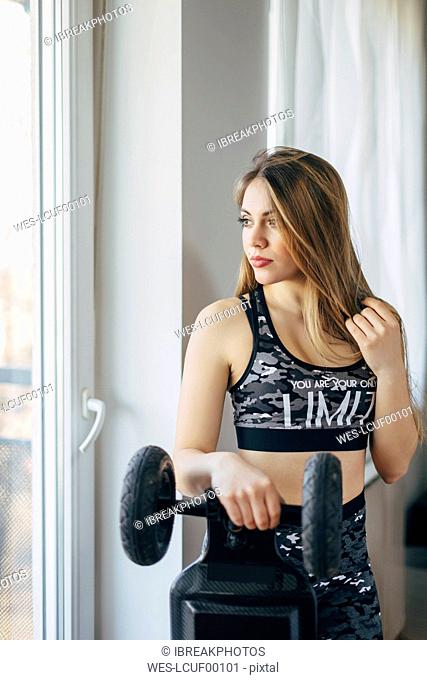 Young woman holding electric skateboard, looking out of window