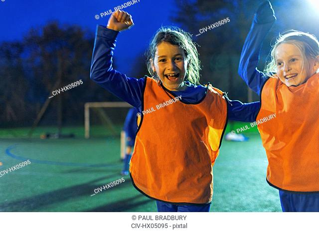 Portrait enthusiastic girl soccer players cheering on field at night
