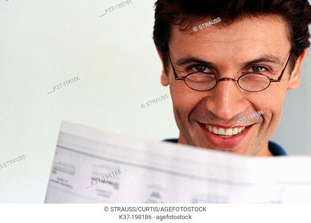Smiling man looking over his newspaper