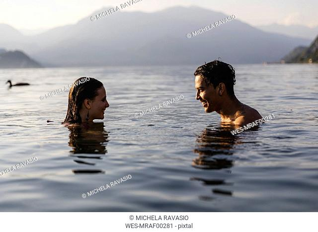Happy young couple in a lake smiling at each other