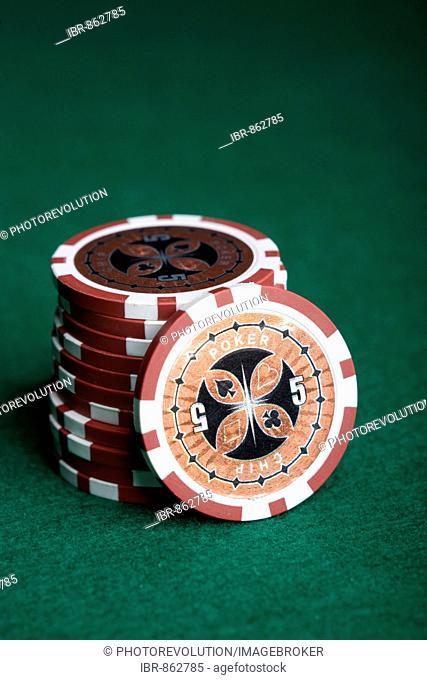 Red poker chips, stacked on green felt
