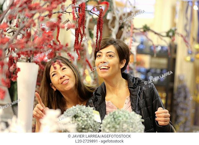 Women buying Christmas ornaments in garden center